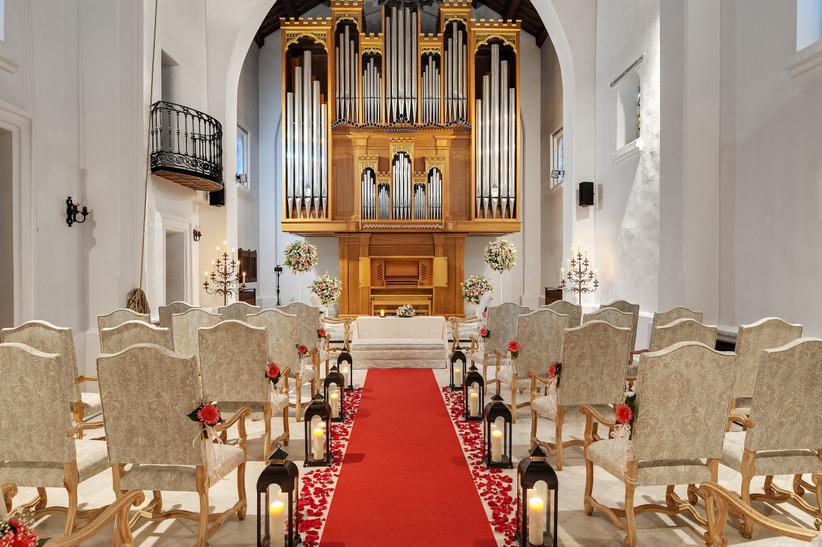Interior de una capilla con butacas y alfombra roja el día de la boda
