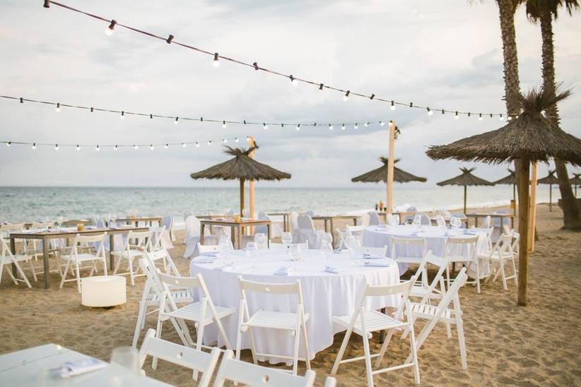 Preparadas las mesas del banquete nupcial en la playa el día de la boda