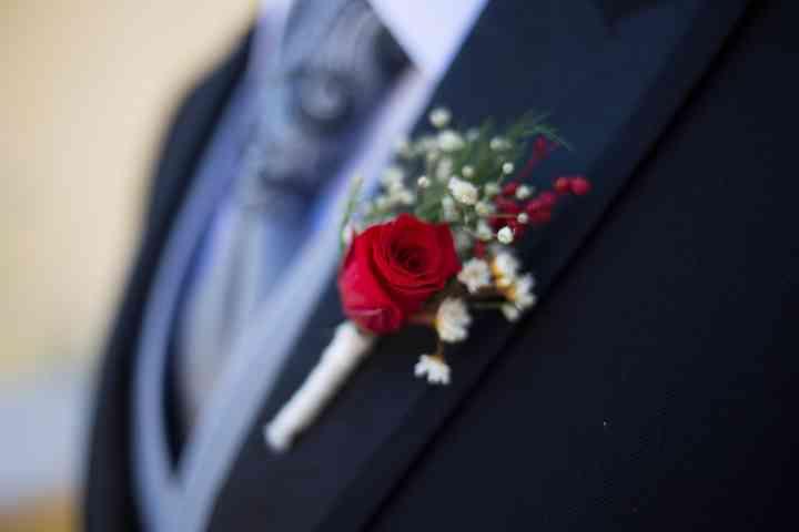 Prendido o boutonnière de rosa en el traje de novio el día de la boda