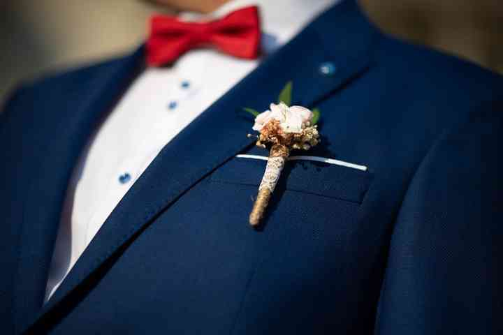 Novio con prendido o boutonnière en el ojal del traje de novio el día de la boda