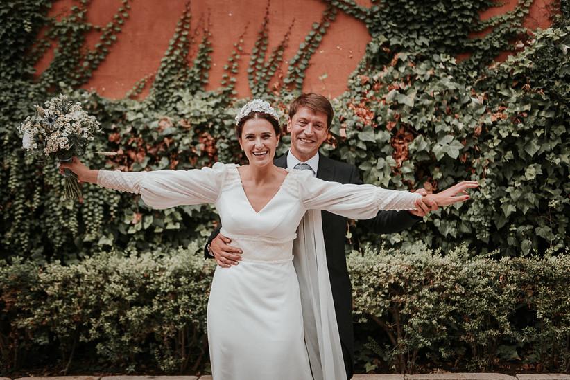 Pareja posa sonriente ante la cámara fotográfica el día de la boda