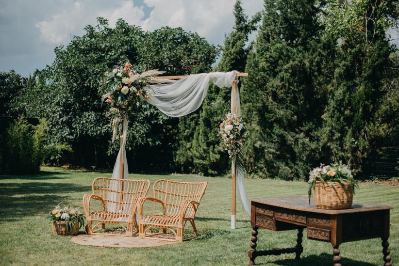 Arco de flores en el altar de la ceremonia con telas livianas de color blanco