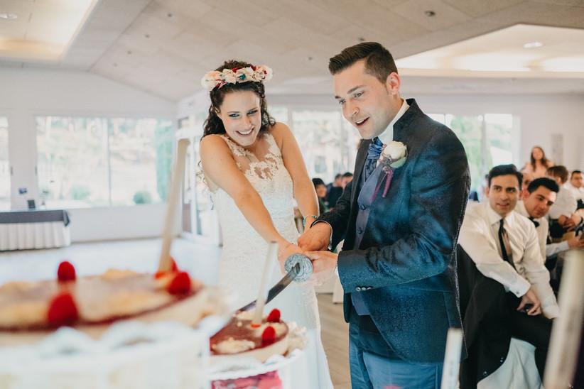 Pareja de recién casados cortando la tarta de boda