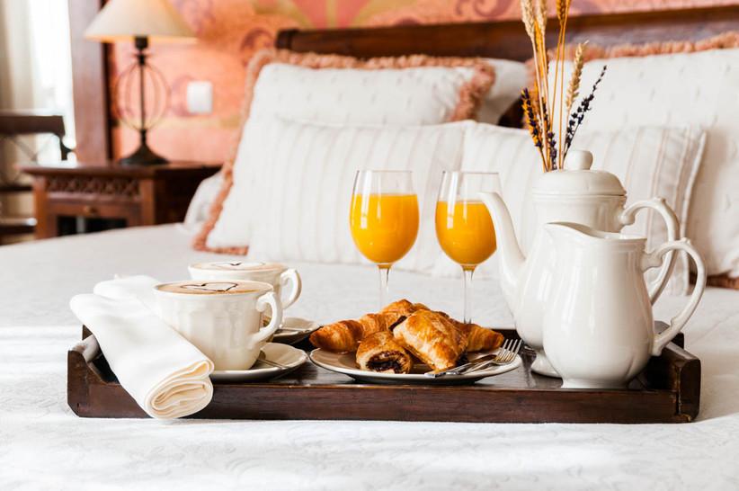 Desayuno para dos en la cama de un hotel