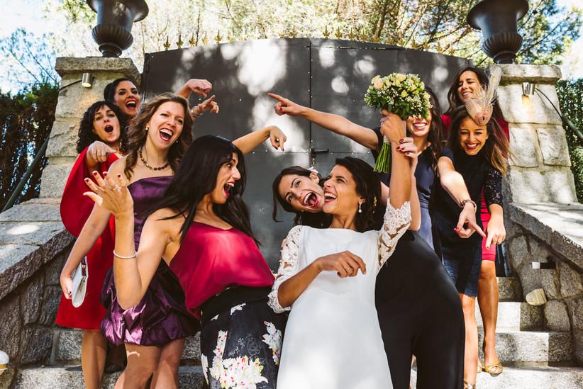Novia rodeada de sus hermanas y amigas el día de la boda, a punto de entregar el ramo de novia