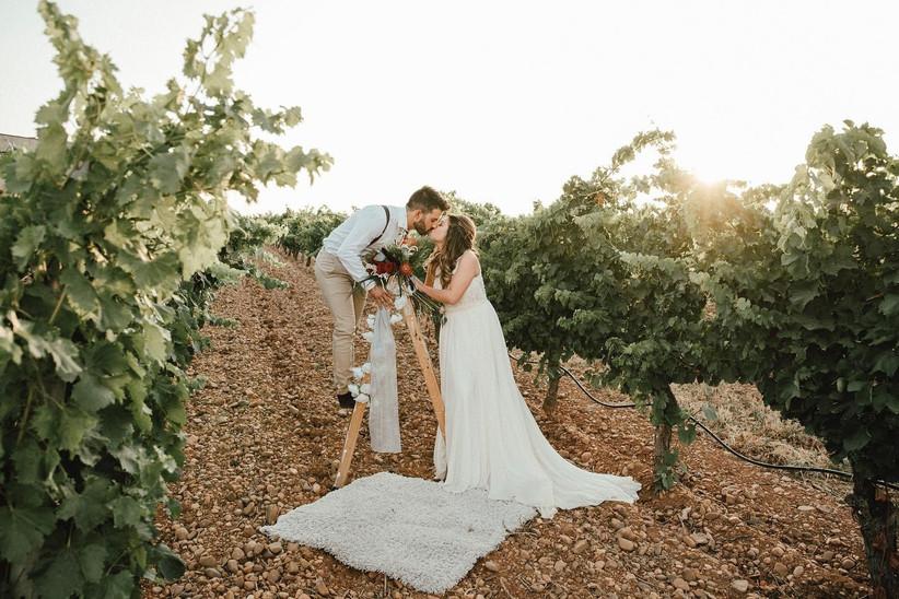 Pareja se besa en un viñedo el día de la boda