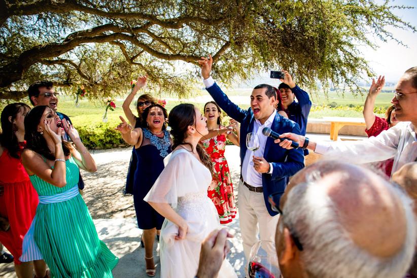 Pareja e invitados disfrutando del baile en una boda de día