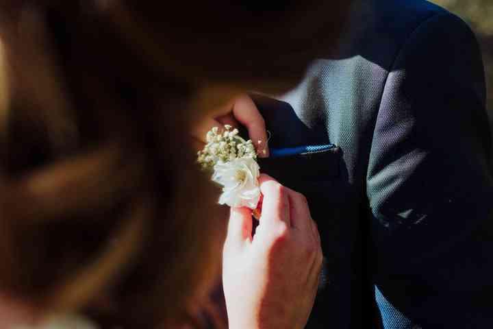 Colocando el prendido o boutonnière en el traje de novio el día de la boda
