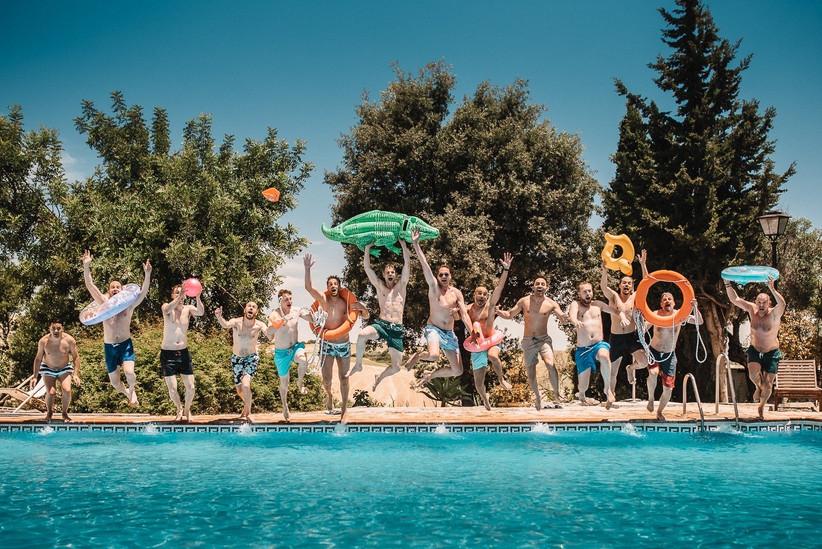Amigos felices se lanzan a la piscina después del día de la boda