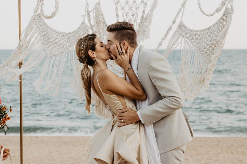 Pareja feliz besándose en el altar de su ceremonia en la playa el día de la boda