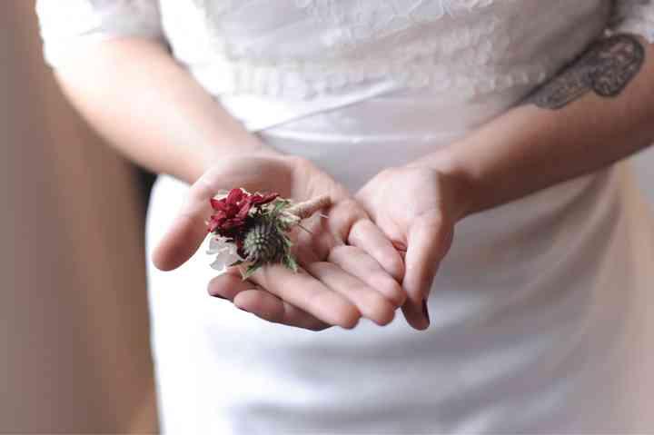 Novia sostiene en sus manos un prendido o boutonnière el día de la boda