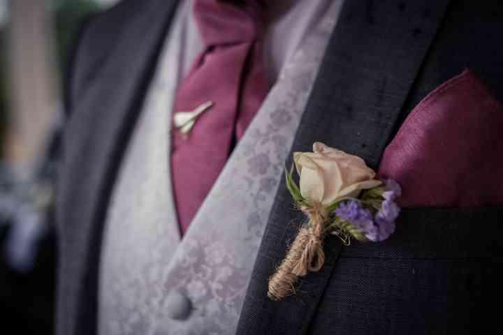 Novio con prendido o boutonnière en tonos crema y morado el día de la boda