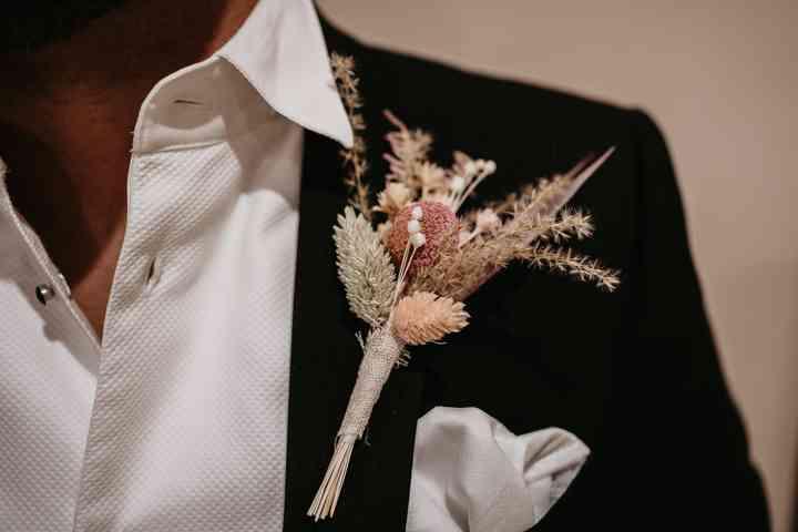 Primer plano del prendido o boutonnière en el traje de novio el día de la boda