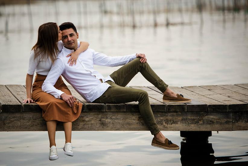Pareja enamorada y feliz sentados en un muelle antes de la boda