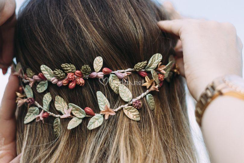 Corona de hojas flores y piñas