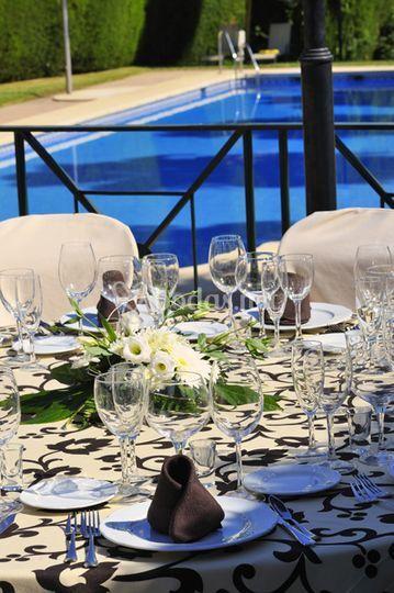 Detalle de las mesas con la piscina de fondo
