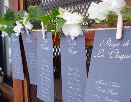 con lista de nombres colgadas con pinzas y rodeadas de flores
